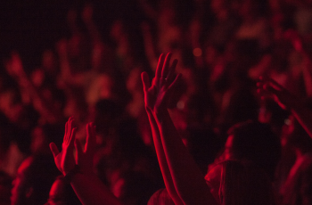 People in crowd with hands in air
